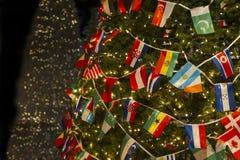 Christasboom met de Vlaggen van het Verscheidenheidsland, Wensend Verenigde Wereld en Vrede royalty-vrije stock fotografie