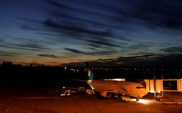 Christchurch New Zealand airport view on a parked airplane. Beatuful late evening sunset blue sky. Night scenery royalty free stock image