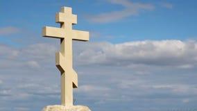 Christelijk kruis op ernstige steen, vreedzame blauwe hemelachtergrond, godsdienst, kerk stock footage