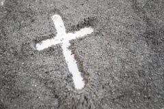 Christelijke kruis of kruisbeeldtekening in as, stof of zand als symbool van godsdienst, offer, redemtion, Jesus Christ, aswoensd stock foto