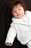 Christening baby boy. Baby boy dressed in a white christening suit, isolated on a black background Royalty Free Stock Photos