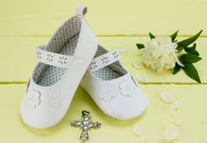 Christening background of white booties and pendant cross on yel Stock Photo