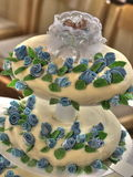 Christening cake. Closeup of decorative tiered christening cake with small baby doll on top Royalty Free Stock Images