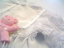 Christening Day. A baby's white christening gown and pink teddybear rattle Royalty Free Stock Image