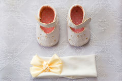 Christening details. On white baby shoes and bandage Royalty Free Stock Photo