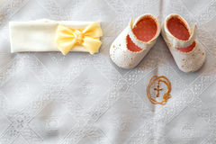 Christening details. On white baby shoes and bandage. Golden cross on a white canvas Stock Photo