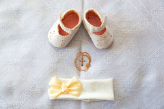 Christening details. On white baby shoes and bandage. Golden cross on a white canvas Stock Photos