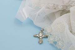 Christening gown with Christian cross pendant isola. Vintage lace christening gown with Christian silver and crystal cross pendant isolated on light blue royalty free stock images