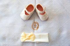 Christening szczegóły Na białym dziecko bandażu i butach Złoty krzyż na białej kanwie zdjęcia stock
