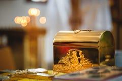 Christening w kościół, złoci religijni naczynia: biblia, krzyż, modlitewna książka, mszał Szczegóły w Ortodoksalnym kościół chrze zdjęcia royalty free