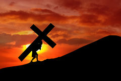 Christian background - man carrying a cross. The figure of a man carrying a heavy cross up a mountain at sunrise or sunset stock photo