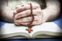 Christian believer praying to God with rosary. In hand royalty free stock photography