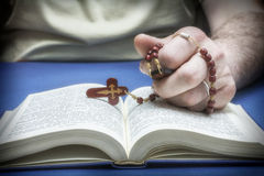 Christian believer praying to God. With rosary in hand royalty free stock image