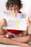 Christian child thanking God. Boy praying,praising and thanking God. Religious kid over a white background Stock Photo