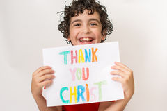 Christian child thanking God. Boy praying,praising and thanking God. Religious kid over a white background