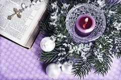 Christian Christmas. Open bibble with Christian cross and Christmas decorative balls, pine and candle stock image