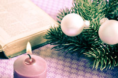 Christian Christmas. Open bibble with Christmas decorative balls, pine and candle Royalty Free Stock Photography