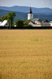 Christian church as an part of village, forested hills in background, yellow field of grain in foreground Royalty Free Stock Photography