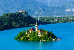 Christian church on island, Bled. With castle and mountains background Stock Photos
