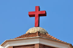 Christian church roof and cross. Roof and red cross of a Christian church architecture under blue sky in Asia, shown as featured element of building and Royalty Free Stock Image