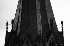 Church tower with the angels. Christian church`s tower with sculptures of angels. Black and white, mystical dark atmosphere. Feelings of the last days of the Royalty Free Stock Image