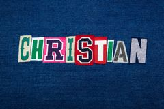 CHRISTIAN collage of word text, multi colored fabric on blue denim, Christianity religion diversity concept. Horizontal aspect royalty free stock photos