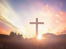 Concept conceptual black cross religion symbol silhouette in grass over sunset or sunrise sky stock images