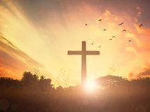 Concept conceptual black cross religion symbol silhouette in grass over sunset or sunrise sky. Christian concept background:Eucharist Therapy Bless God Helping stock photography