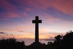 Christian cross. Sun sets on the stone cross at Dodman Point, Cornwall royalty free stock image