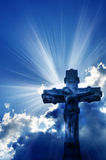 Christian cross. Beams of sunlight coming out from behind clouds and a Christian cross stock images