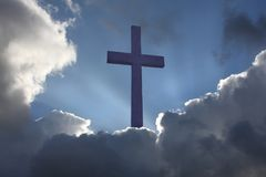 Christian Cross. Coming out of clouds stock images