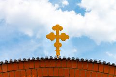 The Christian cross adorns the structure of the temple against t. The yellow Christian cross adorns the structure of the temple against the blue sky with white royalty free stock images