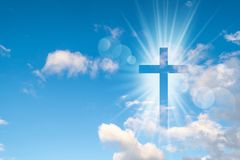 Christian cross appears bright in the sky. Background stock photos