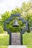 Christian cross with bell inside on green grass background. Christian cross with a bell inside on a green grass background on a sunny day stock images