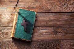Christian cross on bible. Closeup of wooden Christian cross on bible Stock Image