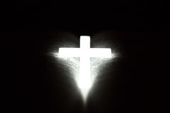 Christian cross on Bible. Glowing phosphor Christian cross on open Bible Royalty Free Stock Image