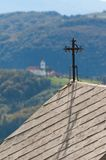 Christian cross on chapel and church in distance. Christian cross on chapel and church on the hill in distance in Slovenia stock photo
