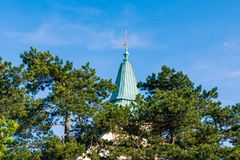 Christian Cross. Which is visible through the pine trees with blue sky. Josefskirche Kahlenberg Vienna, Austria, 2018 Royalty Free Stock Photo