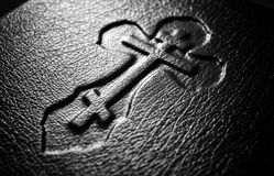 Christian cross. Closeup of Christian cross embossed on holy Bible Stock Images