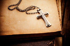 Christian cross. Closeup of silver Christian cross on bible royalty free stock photos