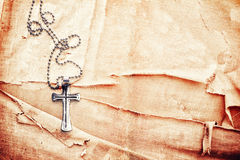 Christian cross. Closeup of silver Christian cross on old canvas Royalty Free Stock Image