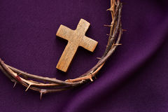 Christian cross and the crown of thorns of Jesus Christ. High-angle shot of a wooden christian cross and the crown of thorns of Jesus Christ on a purple drapery Stock Image
