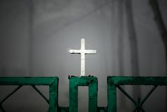Christian cross on fence. Closeup of christian cross - a detail on fence stock photography