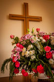 Christian cross and flowers on altar. Christian cross, altar, candle and flower bouquet in a church chapel Royalty Free Stock Photography