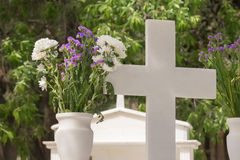 Christian cross on a grave with a flower next to it. Stock Photography