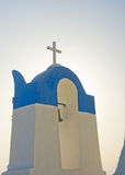 Christian cross in Greece. An image detail from a Greek church of a bell tower and simple Christian cross with a pale yellow aura. There is a suggestion of the stock photography