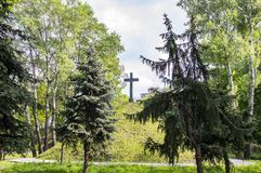 Christian cross on a green hill hill under a cloudy sky stock photography