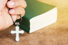Christian cross in hand with bible background. Close up christian cross in hand with bible background Stock Photos