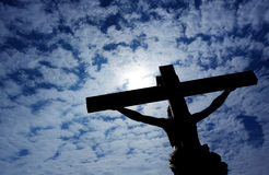 Christian cross with Jesus Christ over cloudy sky Royalty Free Stock Photography