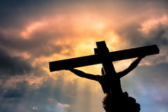 Christian cross with Jesus Christ statue over stormy clouds Stock Images